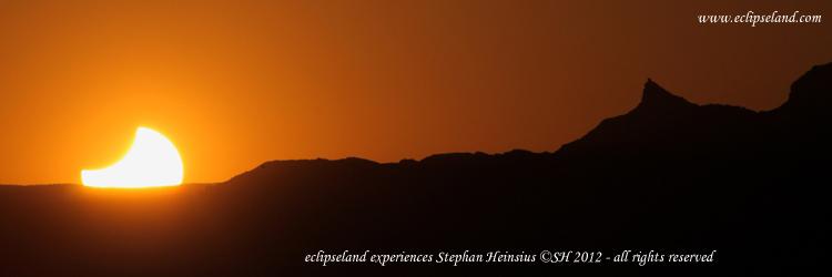 Sonnenfinsternisuntergang neben einer Bergspitze